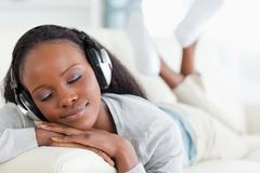 Close up of woman enjoying music on sofa Stock Photos