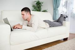 Handsome man lying on a couch using a laptop - stock photo