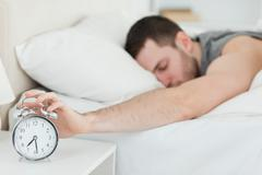 Exhausted man being awakened by an alarm clock - stock photo