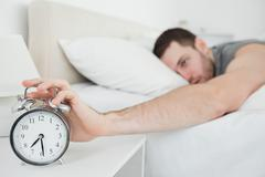Young man being awakened by an alarm clock - stock photo