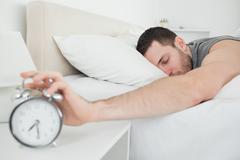 Sleeping handsome man being awakened by an alarm clock - stock photo
