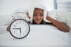 Woman being awakened by her alarm clock in her bedroom - stock photo
