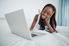 Stock Photo of Young woman watching a movie on her notebook