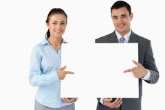 Business partners presenting sign together Stock Photos
