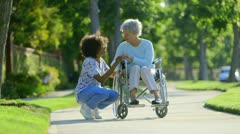 Nurse talking with elderly woman in wheelchair Stock Footage
