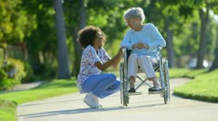 Nurse talking with elderly woman in wheelchair - stock footage