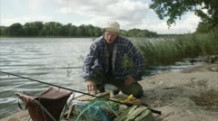 A man grilling his newly caught fish Stock Footage
