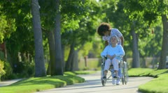 Nurse walking with elderly woman in wheelchair Stock Footage