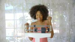 Young woman recording weight loss on scale - stock footage