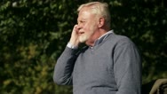 An elderly man with a cellphone in a park Stock Footage