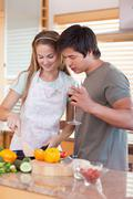 Portrait of a couple cooking while drinking wine - stock photo