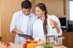 In love couple using a tablet computer to cook - stock photo