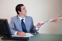 Stock Photo of Businessman giving paperwork to colleague
