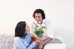 Man giving his girlfriend flowers Stock Photos