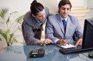 Businessman taking notes while getting mentored by colleague Stock Photos