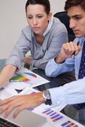 Business team analyzing charts together - stock photo