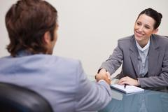 Businesswoman welcomes customer in her office - stock photo