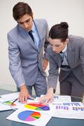 Business partners looking at statistics together - stock photo