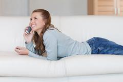 Stock Photo of Young woman on the sofa having a nice conversation on the phone