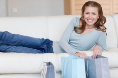 Stock Photo of Smiling female lying next to her shopping