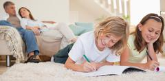 Stock Photo of Siblings doing their homework on the carpet with parents behind them