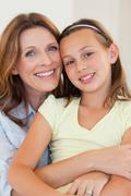 Smiling mother and daughter hugging - stock photo