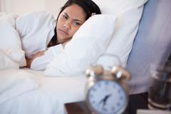 Side view of woman being woken by alarm clock - stock photo