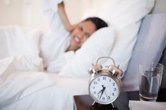 Alarm clock making woman cover her ears Stock Photos