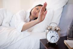 Alarm clock being turned off by woman Stock Photos