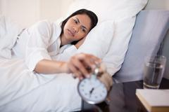 Woman annoyed by ringing alarm clock Stock Photos