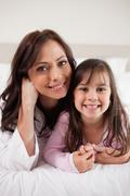 Stock Photo of Portrait of a mother and her daughter lying on a bed