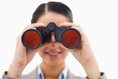 Close up of a businesswoman looking through binoculars - stock photo
