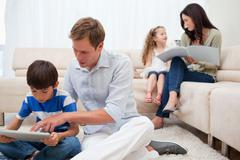 Family spending spare time in the living room - stock photo