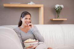 Woman eating popcorn while watching movie - stock photo