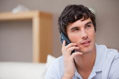 Stock Photo of Man on the cellphone sitting in the living room