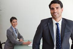 Stock Photo of Good looking businessman posing while his colleague is working
