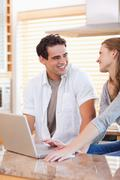 Smiling couple with laptop in the kitchen - stock photo