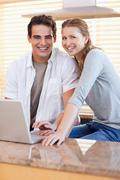 Smiling couple with notebook in the kitchen - stock photo
