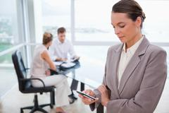 Stock Photo of Standing real estate agent with cellphone