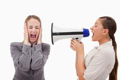 Stock Photo of Young manager yelling at her employee through a megaphone