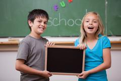 Happy pupils holding a school slate - stock photo