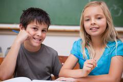 Smiling pupils working together - stock photo