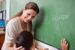 Smiling schoolteacher helping a schoolboy doing an addition - stock photo