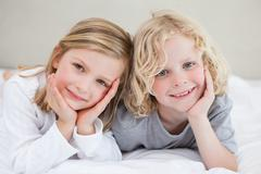 Brother and sister lying on the bed - stock photo