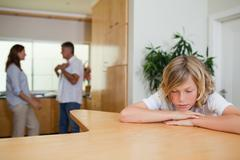 Sad boy has to listen to fighting parents - stock photo