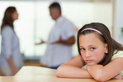 Sad girl with fighting parents behind her - stock photo