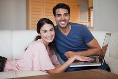 Stock Photo of Lovely young couple using a notebook