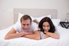 Happy couple laying on the bed together Stock Photos