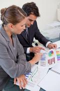 Portrait of an attractive business team studying statistics - stock photo