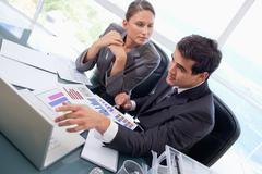 Business team studying statistics with a laptop - stock photo